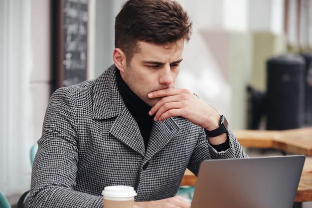 Photo of businesslike man working with silver laptop in cafe outside, drinking takeaway coffee
