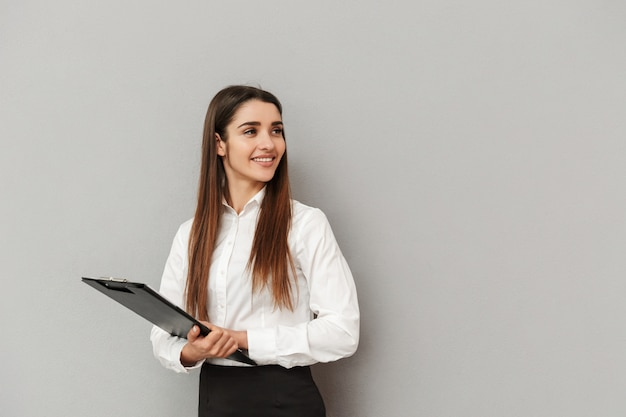 Photo of businesslike woman in white shirt and black skirt holding clipboard with documents in office and looking aside on copyspace, isolated over gray wall