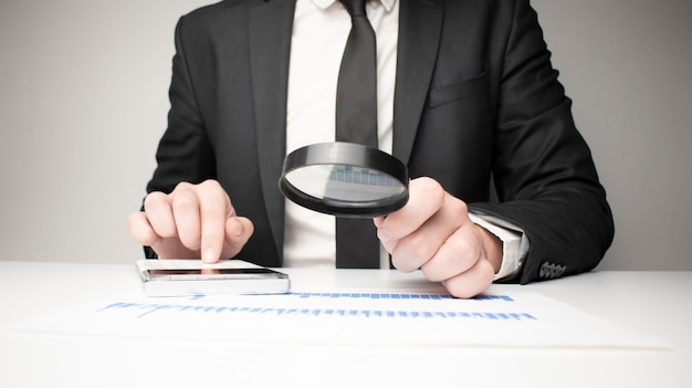 Photo of businessman analyzing bills with magnifying glass