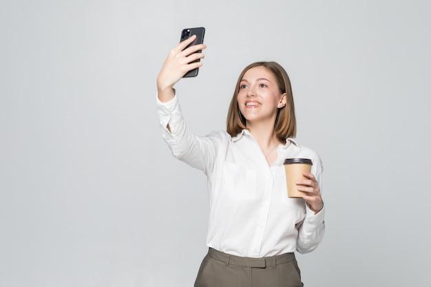 Foto di imprenditrice in abbigliamento formale in piedi tenendo in mano il caffè da asporto e tenendo selfie sul telefono cellulare