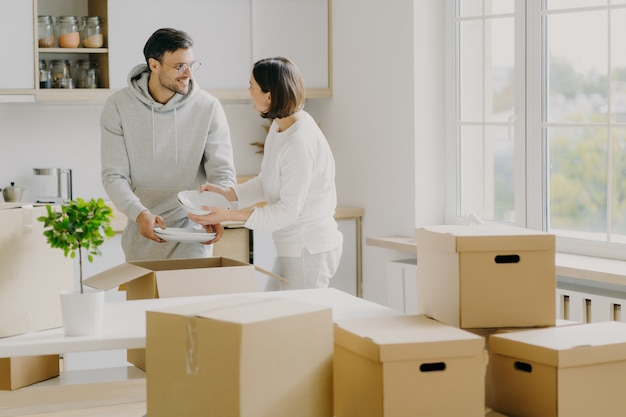 Photo of busy family couple unpack personal stuff from carton boxes, dressed in casual clothes, hold white plates, pose in spacious kitchen with modern furniture, surrounded with pile of packages