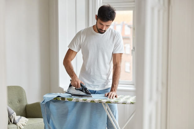 Photo of busy unshaven man irons shirt on ironing board, prepares for formal meeting on business conference