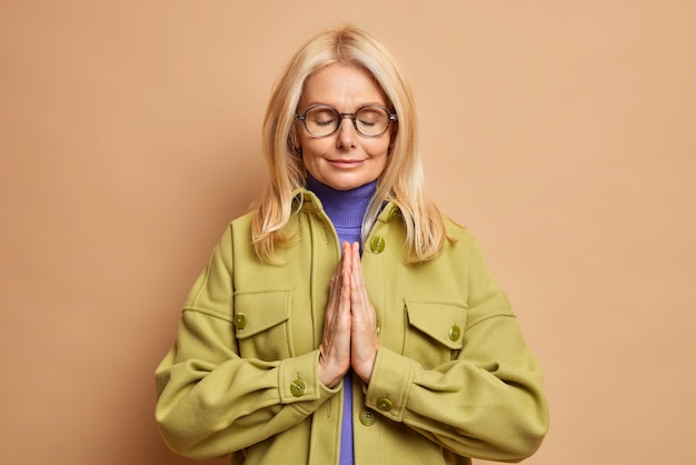 Photo of calm senior blonde woman prays for good wellness of her family stands with closed eyes and palms pressed together wears spectacles and stylish jacket asks god to help dreams come true