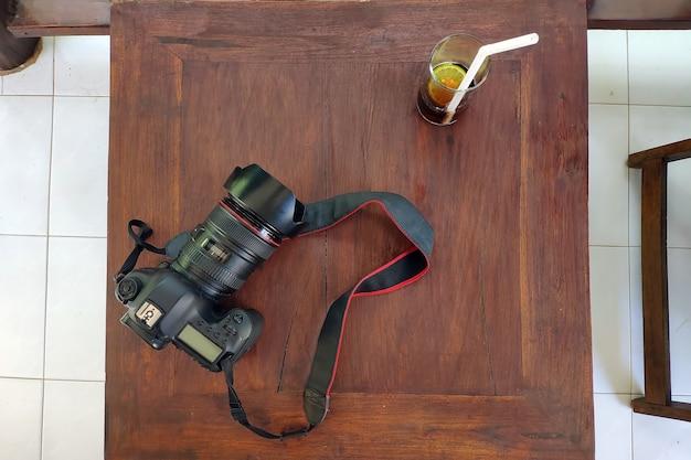 写真カメラと木製のテーブルにレモンとコーラのガラスフラットは屋外に横たわっていた