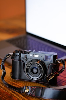Photo camera in a black leather case, on a dark wooden table. next to the laptop. workplace and accessories of the photographer or a freelancer