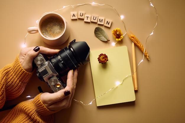 フォトカメラ、コーヒー、オレンジのニットセーター