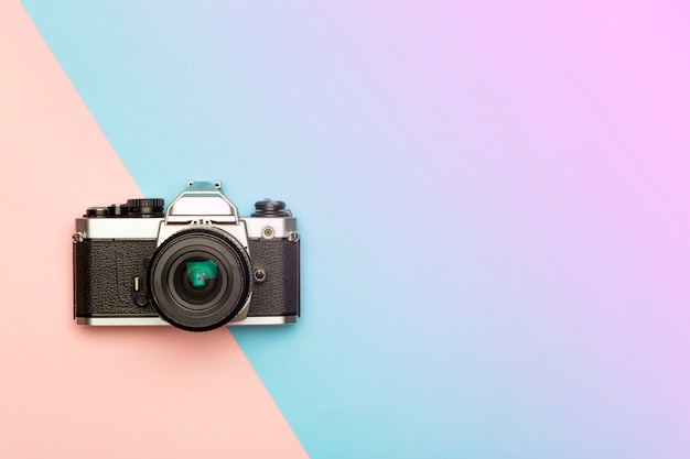 Photo camera creative concept background. vintage retro photo camera on a colored background. travel, vacation and photography concept