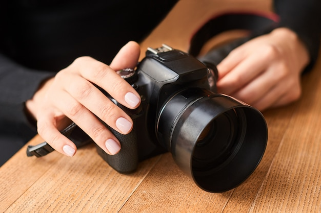 Photo camera in hand on wooden table in international photographer day