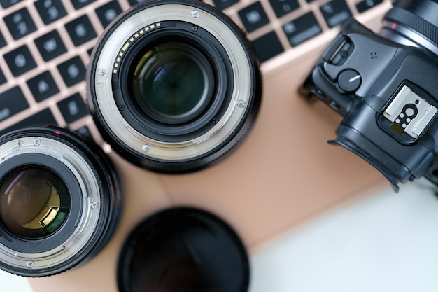 Объективы для фотоаппаратов с ноутбуком на рабочем столе, работающим фотографом и зарабатывающим деньги