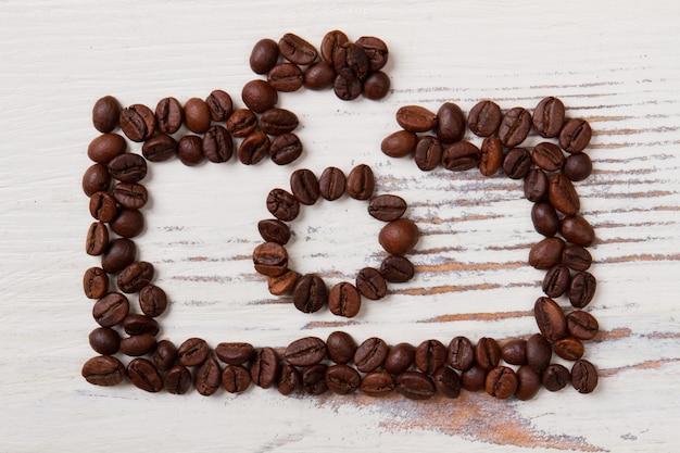 흰색 나무에 커피 콩으로 만든 사진 카메라. 커피 곡물 예술.