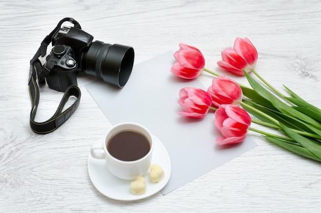 Photo camera, mug of coffee and pink tullips