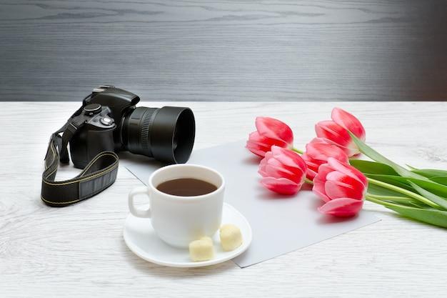 写真のカメラ、コーヒーのマグカップ、ピンクのチューリップ。木製の背景