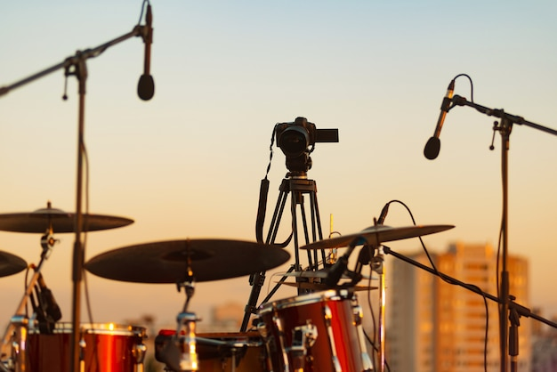 A photo of a camera near a drum kit and a microphone on the stage