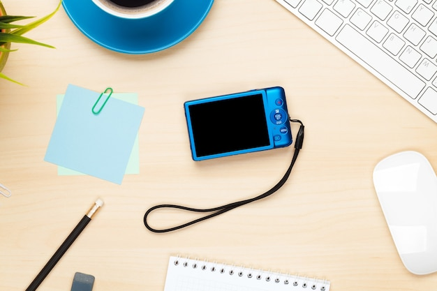 Photo camera on office table with notepad, computer and coffee cup. view from above