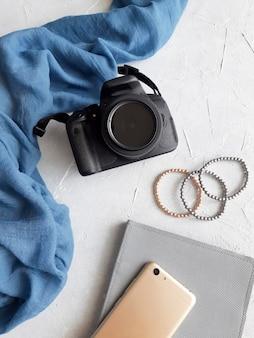 사진 카메라 스카프 전화 노트북과 팔찌는 콘크리트 배경에 평평하게 놓여 있습니다.