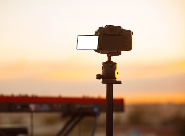 Photo of camera with empty blank screen filming live concert outdoor