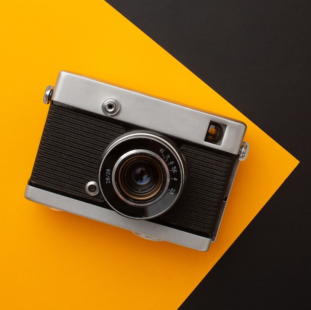 Photo camera on a yellow and black background with a place for your inscription. high quality photo