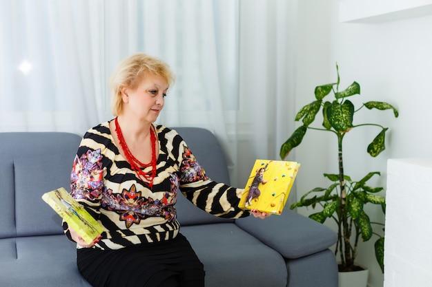 フォトキャンバス。写真の帆布を撮っている間やる気を感じる金髪の年配の女性