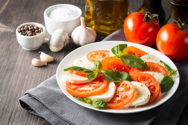 Photo of caprese salad with tomatoes, basil, mozzarella, olives and olive oil. italian traditional caprese salad ingredients. mediterranean, organic and natural food concept.