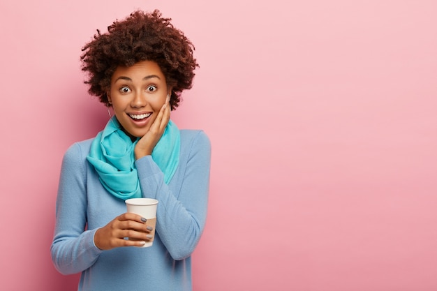 Photo of carefree curly woman holds disposable cup of coffee, enjoys drinking aromatic beverage, wears blue casual clothes, has free time after work, poses over rosy wall, copy space for your advert