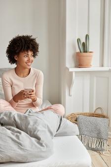 Foto di spensierata donna dalla pelle scura vestita in indumenti da notte, tiene il cellulare, condivide messaggi con gli amici, posa sul letto sfatto, felice di ricevere una notifica con buone notizie. biancheria da letto e concetto di riposo