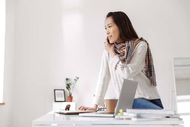 Photo of casual asian female worker wearing white sweater reading business diary and smiling while sitting on table in office