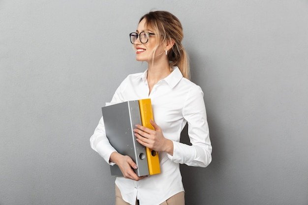 Photo of caucasian businesswoman wearing glasses holding paper folders in the office, isolated