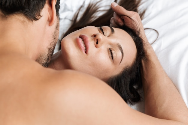 Photo of caucasian couple man and woman hugging together, while lying in bed at home or hotel apartment