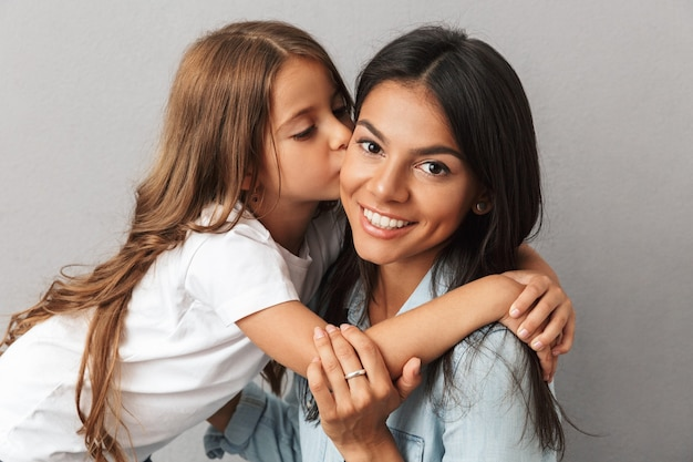 Photo of caucasian family little daughter hugging and kissing her mother on cheek, isolated over gray
