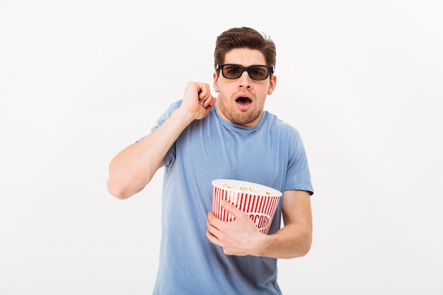 Photo of caucasian guy in casual t-shirt and 3d glasses eating popcorn and emotionally watching movie in cinema, isolated over white wall