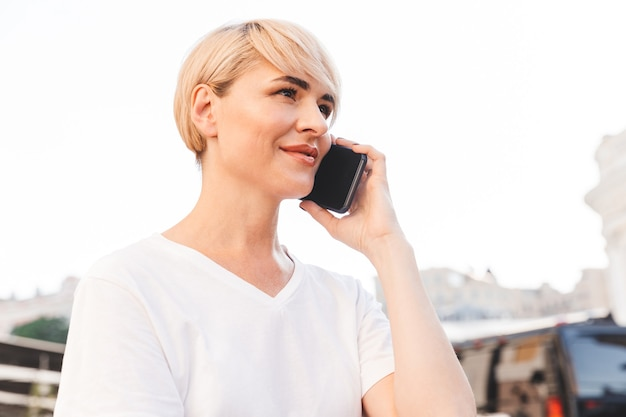 Photo of caucasian joyful woman wearing white t-shirt sitting in summer cafe outdoor, and talking on cell phone