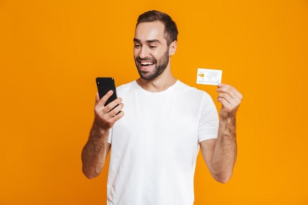 Photo of caucasian man 30s in casual wear holding smartphone and credit card, isolated