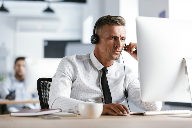 Photo of caucasian man 30s wearing office clothes and headset, sitting by computer in call center