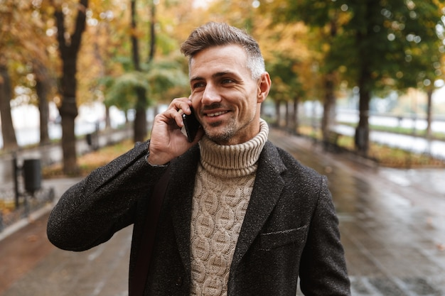 Photo of caucasian man 30s wearing warm clothes walking outdoor through autumn park, and using mobile phone