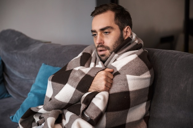 Photo of caucasian man 30s wrapped in blanket having temperature and looking sick while sitting on sofa in apartment