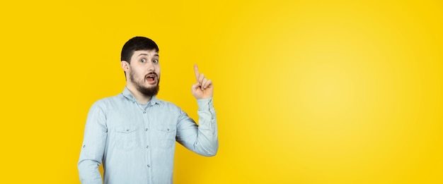 Photo of caucasian man  reliable person got new brilliant idea, startup raise finger, wear jeans denim shirt  over yellow background, panoramic mock-up