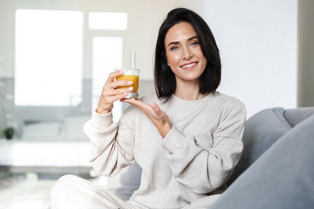 Photo of caucasian woman 30s drinking orange juice, while sitting on sofa in bright room