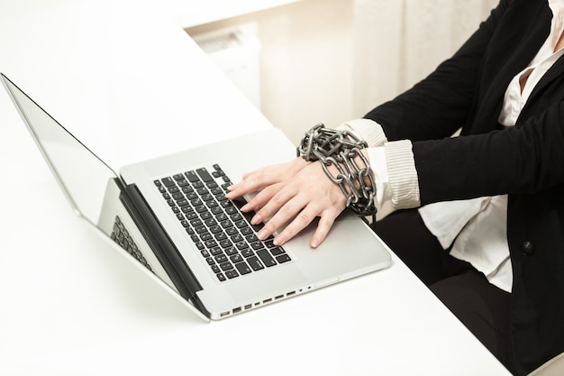 Photo of chained businesswoman typing on keyboard