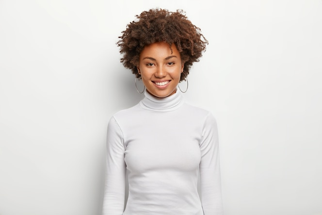 Photo of charismatic lovely woman with curly hair, has fun, toothy smile on face