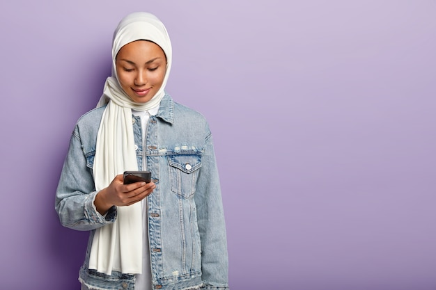 Foto della signora musulmana charmimg concentrata nel moderno dispositivo smartphone