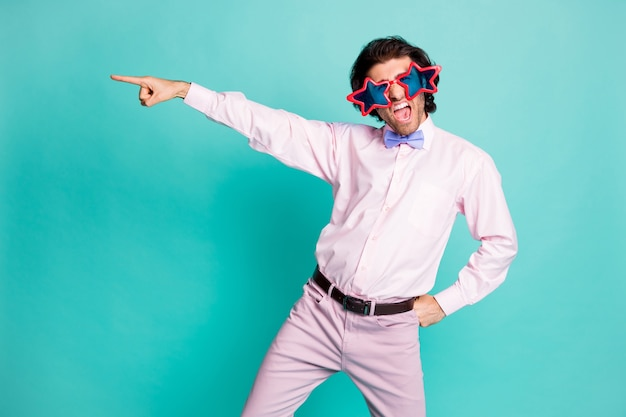 Photo of charming brunet wavy hair gentleman dressed pink shirt dancing pointing one finger empty space isolated turquoise color background