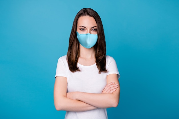 Photo of charming confident lady arms hands crossed bossy worker intelligent person successful career team member wear casual medical mask white t-shirt isolated blue color background