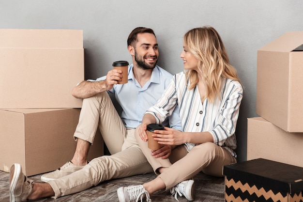 Photo of charming couple in casual clothing seating near cardboard boxes and holding paper cups isolated over gray wall