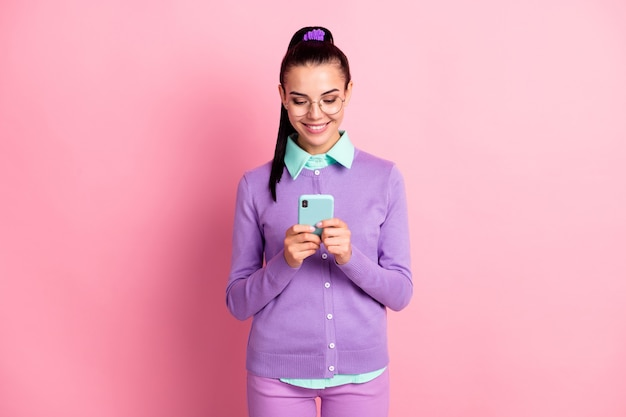 Photo of charming girl hold telephone look screen wear specs purple cardigan isolated pink color background