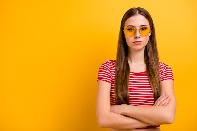 Photo of charming gorgeous self-assured young girl folded arms almost angry dissatisfied disagree canceled pool party wear sun specs striped white red shirt vivid yellow color background