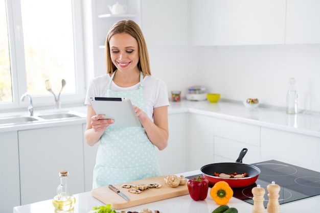 Photo of charming housewife enjoy weekend morning cooking holding e-reader checking recipe steps online cook book stand white light kitchen indoors