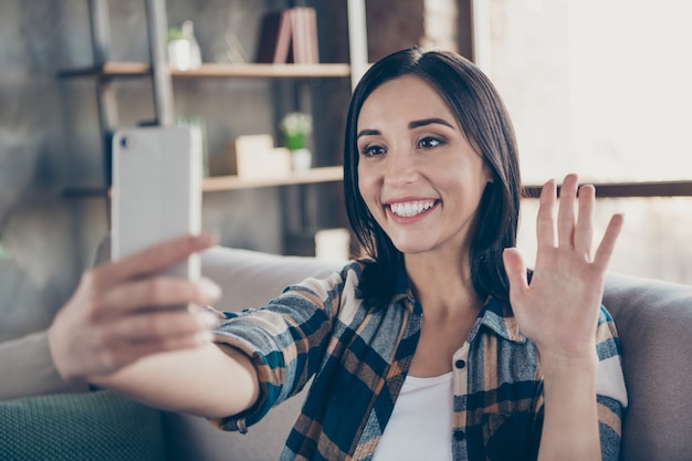 Photo of charming lady holding telephone making selfies speaking skype waving palm saying hi sitting comfort sofa wear casual checkered shirt apartment indoors