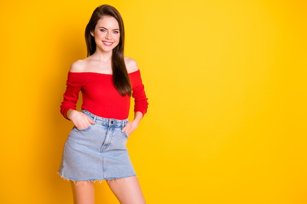 Photo of charming lovely self-assured young girl hands pockets beaming smile prepare train youngsters wear shirt uncovered shoulders denim mini skirt isolated vivid yellow color background
