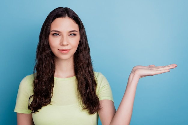 Photo of charming pretty confident girl hand hold invisible object promoting on blue background