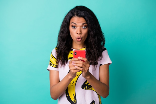 Photo of charming surprised young lady hold telephone funny face wear banana print t-shirt isolated turquoise color background